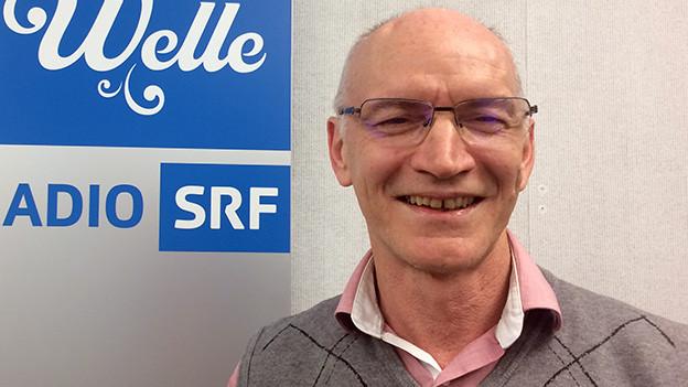 Ein lachender Mann steht vor dem blau-weissen Logo von SRF Musikwelle.