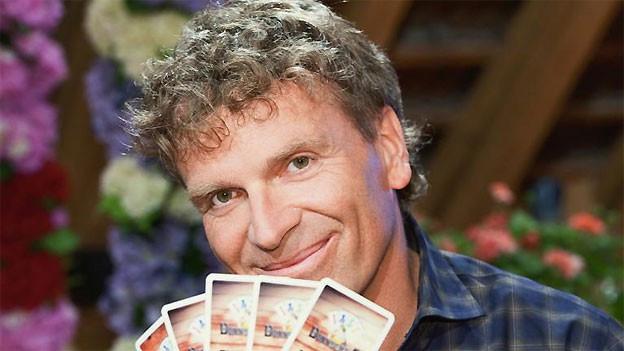 Der Jass-Experte hält ein paar Karten in der Hand.
