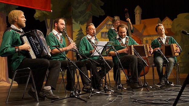 Volksmusikanten in grünen Sennenhemden beim Musizieren auf einer Bühne.