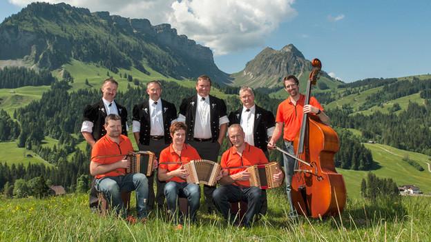 Jodlerformation und Schwyzerörgeligruppe vereint auf Alpwiese.