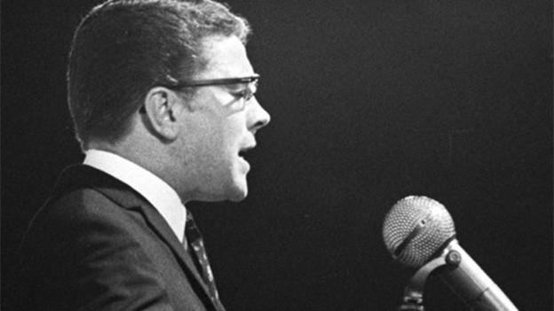 Der Komponist steht singend vor einem Mikrofon.