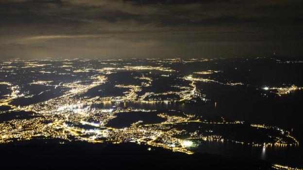 Vogelperspektive über Stadt bei Nacht.