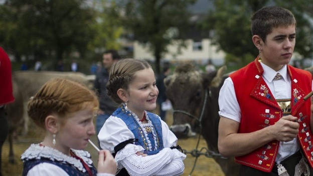 zwei Mädchen in Appenzeller Tracht betrachten Jungen in appenzeller Tracht