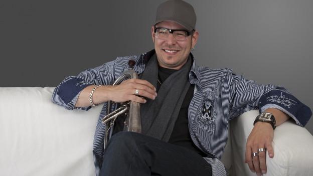 Dirigent in jugendlichem Outfit mit Jeans Ketten und Baseball-Cap.