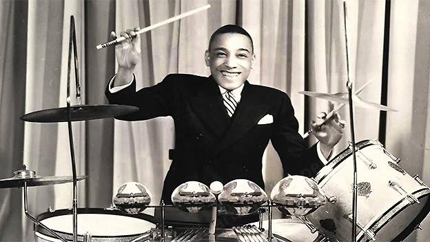 Schwarz-Weiss-Fotografie mit dem jungen fröhlichen Schlagzeuger hinter seinem Instrument.