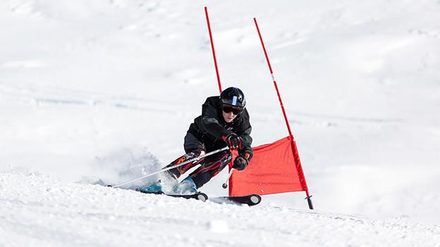 Ein Skifahrer fährt an einer rot beflaggten Slalomstange vorbei.