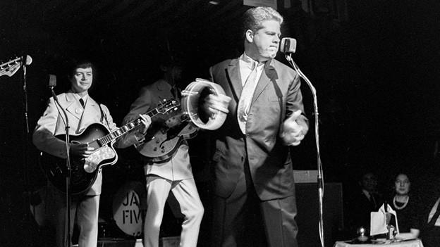 Schwarz-Weiss-Fotografie mit dem Sänger während eines Auftritts.