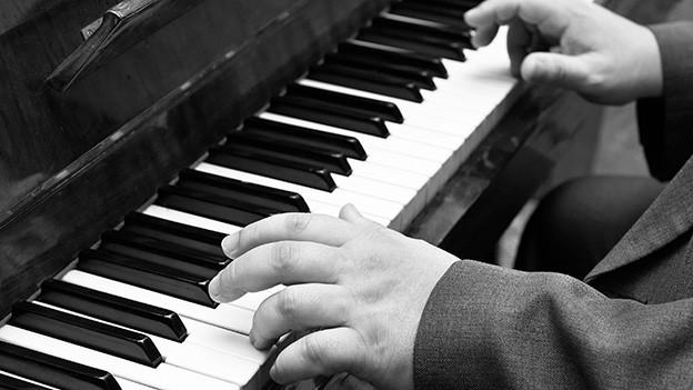 Schwarz-Weiss-Fotografie von einem Klavier.