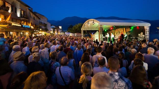 Menschen an vor Konzertbühne direkt am Pier beim Lago Maggiore.