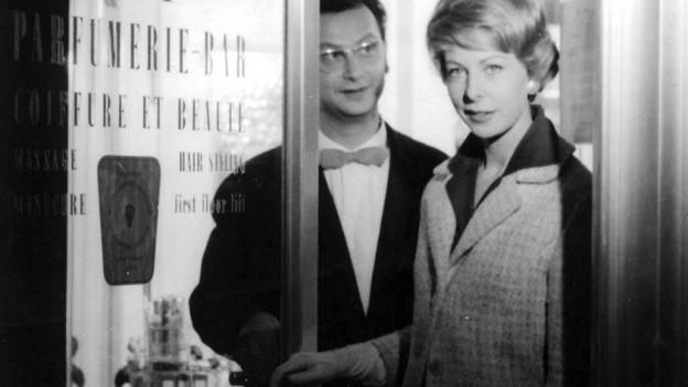 Zwei Schauspieler beim Verlassen einer Parfümerie.