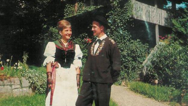 Jodelpaar auf Alpwiese vor Hütte.
