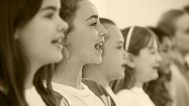 Auf alt getrimmtes Bild von singenen Mädchen.