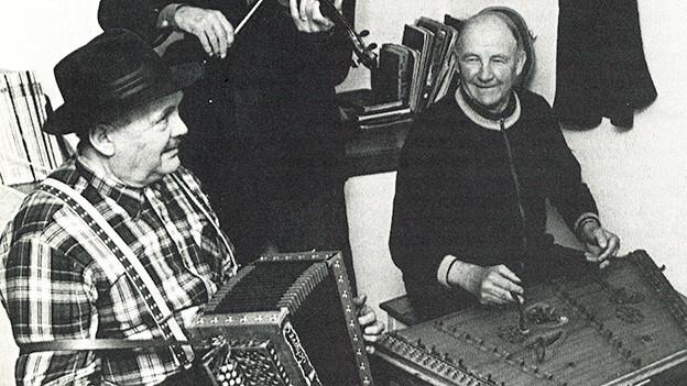 Schwarz-Weiss-Fotografie mit zwei Männern, die Schwyzerörgeli und Hackbrett spielen.
