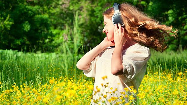 Eine junge Frau trägt Kopfhörer und steht in einer Sommerwiese.