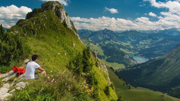 Bergsteiger sitzt auf Bergspitze und blickt hinunter ins Tal.