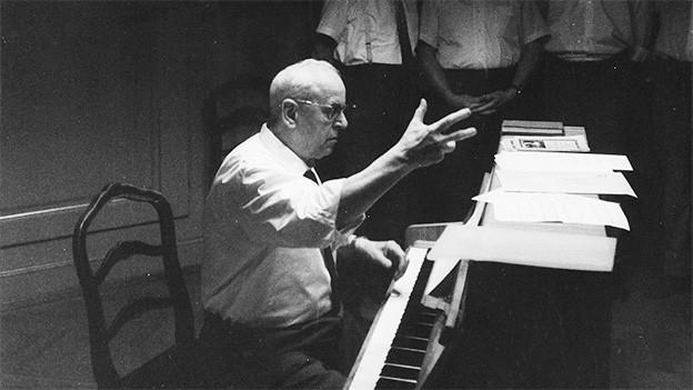 Ein Dirigent sitzt an einem Flügel und leitet einen Chor.