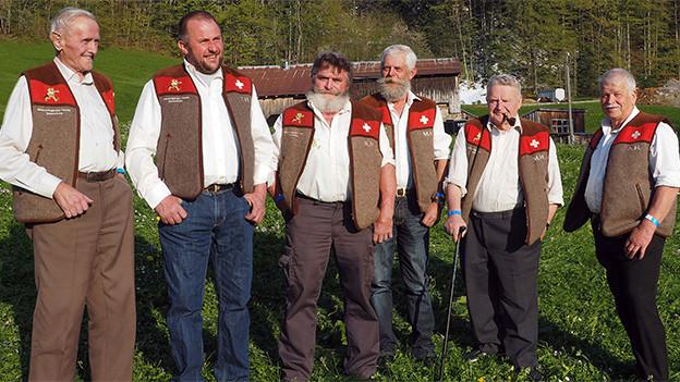Sechs Männer in weissen Hemden und braun-roten Gilets stehen nebeneinander auf einer Wiese.