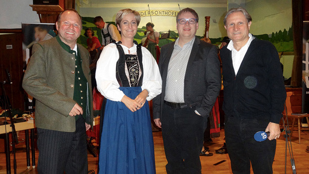 Gruppenbild mit drei Männern und einer Frau vor einer Bühne.