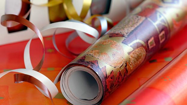 Eine Rolle Geschenkpapier mit farbigen Bändern.