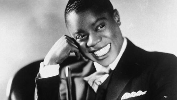 Schwarzweissfoto eines schwarzen Musikers im Anzug mit Trompete.