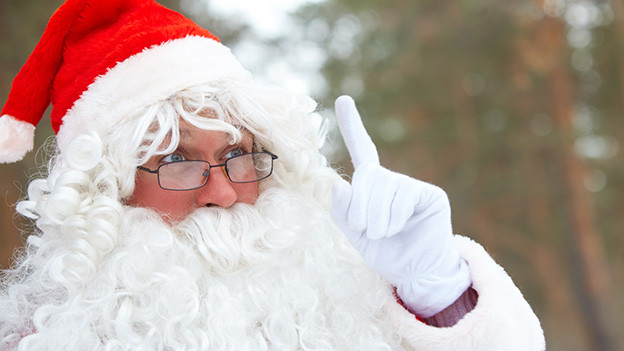 Ein Weihnachtsmann mit rotem Gewand, weissen Haaren, weissem Bart und Brille.