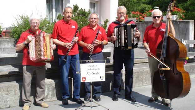 Ländlerquintett posiert in roten T Shirt und mit Instrumenten.