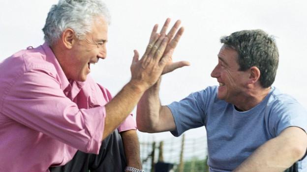 Zwei Senioren klatschen sich in die Hände.