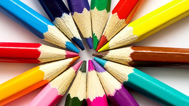 Verschiedene Farbstifte kreisförmig ausgelegt.