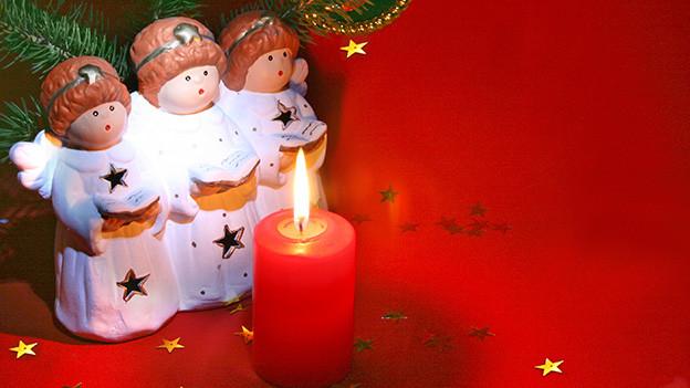 Drei kleine Engel aus Ton vor einer roten Kerze.