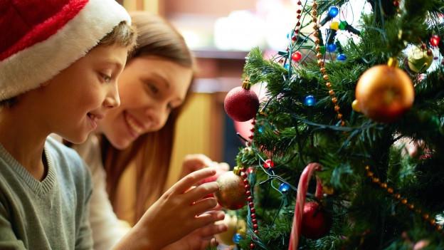 Zwei Kinder schmücken den Weihnachtsbaum.