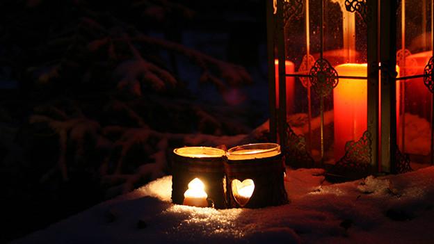 Zwei Kerzen vor einer Laterne in einem Wald.