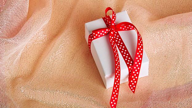 Ein kleines Geschenk mit roter Schleife.
