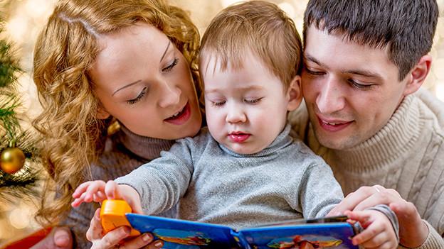 Eltern schauen sich mit ihrem Kleinkind ein Buch an.