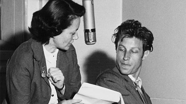 Schwarz-Weiss-Fotografie von einer Frau, die sich mit einem Mann unterhält.