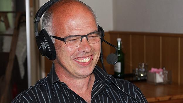 Ein Mann im gestreiften Hemd sitzt mit Kopfhörern vor einem Mikrofon.