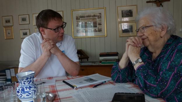 Reporter mit Seniorin in Wohnzimmer.