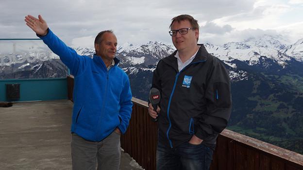 Ein Mann mit einer hellblauen Jacke und einer mit einer grau-braunen Jacke auf der Terrasse eines Berghauses.