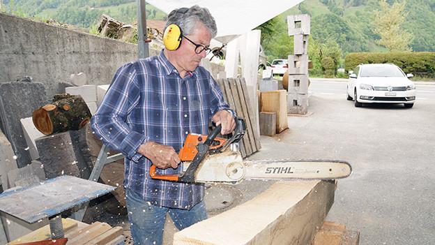 Der Bildhauer bearbeitet ein Stück Eichenholz mit einer Motorsäge.