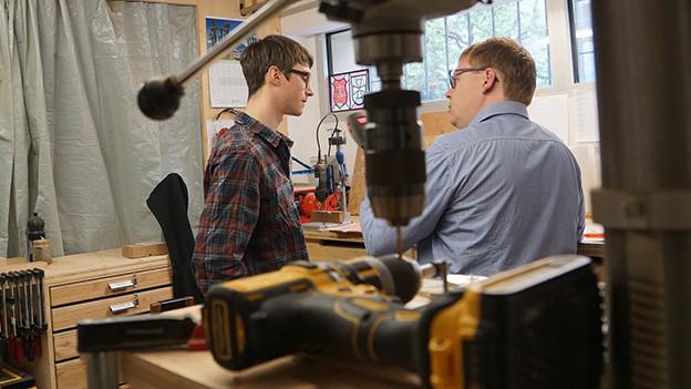 In der Werkstatt des Schreiners unterhalten sich zwei Männer.