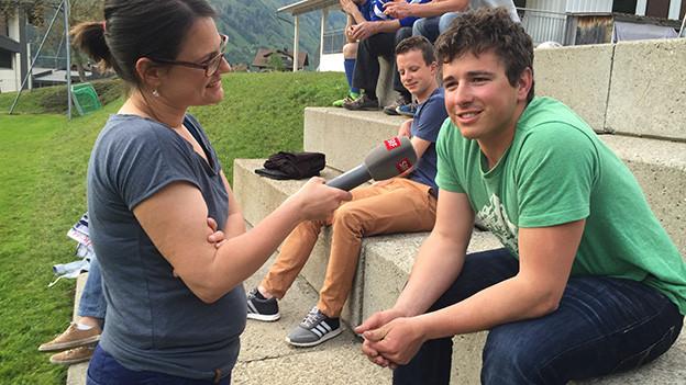 Die Reporterin unterhält sich mit einem jungen Fussballspieler.
