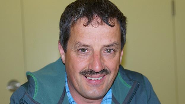 Ein Mann mit Schnurrbart und blauer Jacke.
