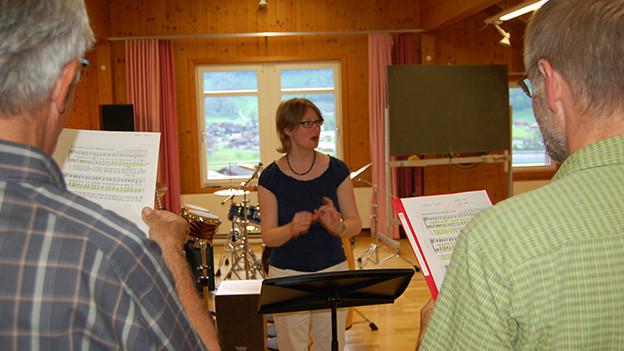 Eine Dirigentin steht vor einer Gruppe von Sängern.