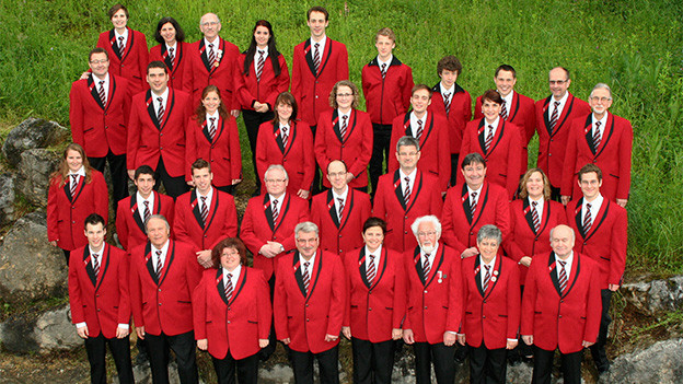 Eine grosse Gruppe von Musikanten in schwarz-roter Uniform.