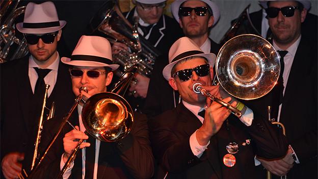 Blasmusikanten mit schwarzen Westen, weissen Hüten und dunklen Sonnenbrillen während eines Auftritts.