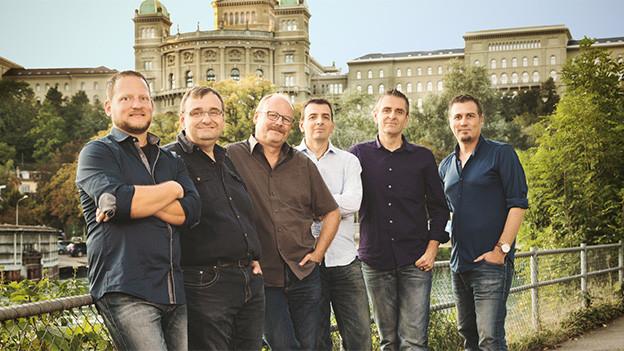 Gruppenfoto mit den sechs Musikern an der Aare in Bern mit dem Bundeshaus im Hintergrund.
