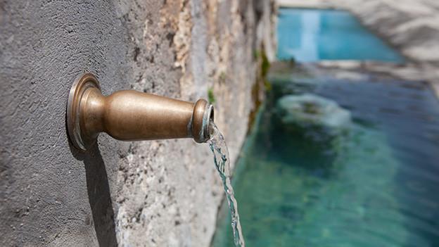 Grossaufnahme von einem Wasserhahn an einem alten Brunnen.
