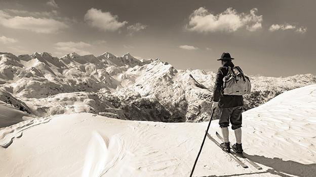 Eine alte Aufnahme mit einem Skifahrer, der auf einem Berg steht mit einer herrlichen Aussicht auf eine Bergpanorama.