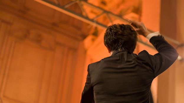 Ansicht von hinten auf einen Dirigenten, der seinen Dirigentenstab schwingt.