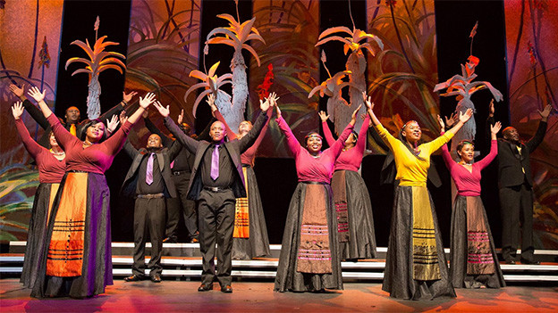 Farbenfrohes Bild mit Gospelsängerinnen und -sängern, die während eines Konzerts ihre Arme in die Höhe strecken.