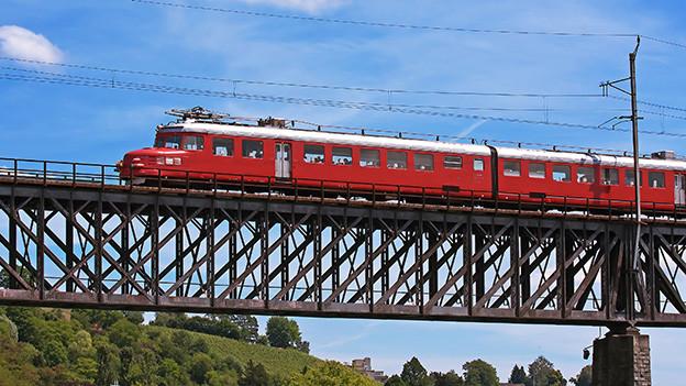 Ein roter Zug fährt über eine Brücke aus Eisen.